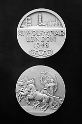 Participation Medals for the competitors at the 1948 London Summer Olympic Games. Made from oxydiced silver instead of gold, 51,0 mm in diameter and weighing 61 gr. Design by B. Mackennal and J. Pinches. The Obverse shows a City view of London over legend in three lines with the Olympic rings below. The reverse depicts a symbolic Grecian chariot. 4,062 competitors will take part in the Olympics.