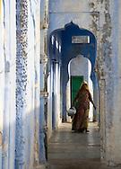A woman walking through a series of blue arches in Pushkar, Rajasthan, India