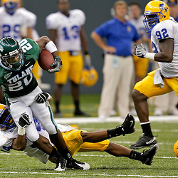 Sep 26, 2009; New Orleans, LA, USA; Tulane Green Wave wide receiver Jeremy Williams (20) is tackled by McNesse State Cowboys safety Malcolm Bronson (34) at the Louisiana Superdome. Tulane defeated McNeese State 42-32. Mandatory Credit: Derick E. Hingle-US PRESSWIRE
