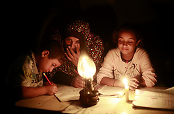 October 2, 2017 - Gaza City, The Gaza Strip, Palestine - A Palestinian woman helps her children study by candlelight in her temporary home during a power outageÃ• in the Khan Yunis refugee camp in the southern Gaza Strip, and 1.8 million people in Gaza suffer from power cuts of about 20 people a day. April, 2017. The Gaza Strip's only power plant has run out of fuel and has been shut down.The Gaza power plant usually operates eight hours a day after fuel passes through Gaza through the Kerem Shalom crossing. (Credit Image: © Mahmoud Issa/Quds Net News via ZUMA Wire)