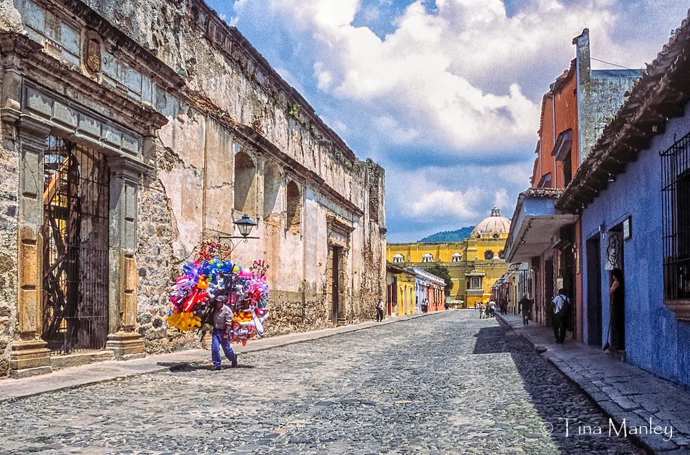 Balloon seller walks down the street in Antigua, Guatemala.