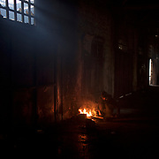 Sadeq, a 13 year old afghan migrant, tends to a fire in one of the abandoned warehouses in central Belgrade, used in recent months as shelter for hundreds of migrants en route to Western Europe.