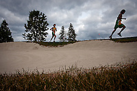 JEROME A. POLLOS/Press..Members of the Lakeland High cross country team run along one of the bunkers at Circling Raven Golf Course as cloudy skies loom overhead.