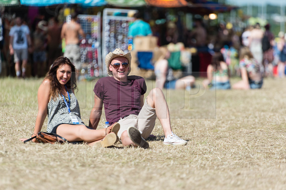 © Licensed to London News Pictures. 13/06/2014. Isle of Wight, UK.   A couple relax in the early morning sun at Isle of Wight Festival 2014 - today is expected to be the hottest day of the year in the UK.   The Isle of Wight festival is an annual music festival that takes place on the Isle of Wight. Photo credit : Richard Isaac/LNP