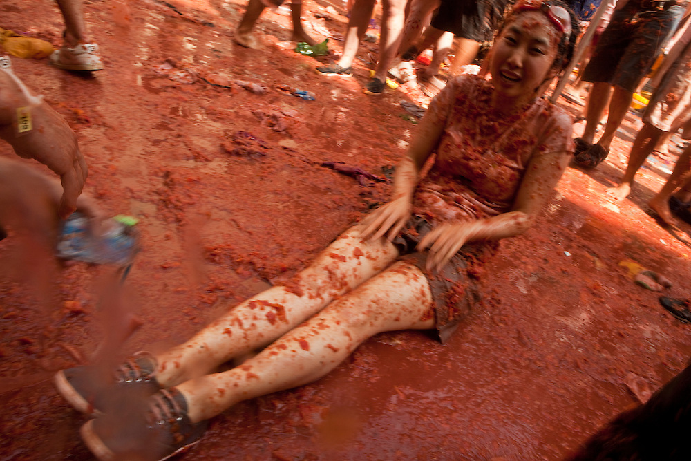 August 31, 2011. An Asian young woman  lays on the floor on a puddle of tomato juice  after an intensive tomato fight during the tomatina. An estimated 35,000 people threw 120 tons of tomatoes in the world's biggest tomato fight held annually the last Wednesday of August in the Spanish town of Buñol, Valencia, Spain.