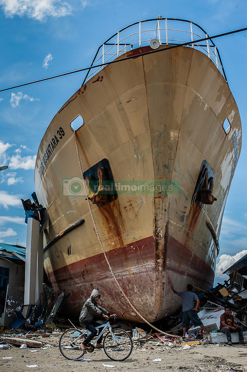 October 6, 2018 - Palu, Central Sulawesi, Indonesia - A man seen cycling in front of a ship that stranded on land after  earthquake and tsunami In Wani village. A deadly earthquake measuring 7.5 magnitude and the tsunami wave caused by it has destroyed the city of Palu and much of the area in Central Sulawesi. According to the officials, death toll from devastating quake and tsunami rises to 1,480, around 800 people in hospitals are seriously injured and some 62,000 people have been displaced in 24 camps around the region. (Credit Image: © Hariandi Hafid/SOPA Images via ZUMA Wire)