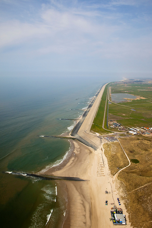 Nederland, Noord-Holland, Gemeente Schoorl, 28-04-2010; Hondsbossche zeewering gezien naar het noorden, Petten en de duinen aan de horizon. Rechts van de zeedijk de Vereenigde Harger- en Pettemerpolder met 'De Putten' (ontstaan in het verleden door het uitgegraven grond om de  zeewering te verstevigen). De dijk is aangelegd als zeewering nadat de oorsrponkelijke duinen weggeslagen waren. Door erosie kalven de duinen langs de kust steeds verder af, de dijk steekt daardoor steeds meer uit in zee..Hondsbossche seawall seen to the north, Petten and the dunes on the horizon. Right side of the seawall and the United Harger Pettemer Polder with 'The Wells' (created in the past by using soil for strengthening the seawall). The dike was built as a seawall after the primal dunes were washed away. Because of erosion the dunes decrease in size, therefore the sewall sticks more and more out into the sea..luchtfoto (toeslag), aerial photo (additional fee required).foto/photo Siebe Swart