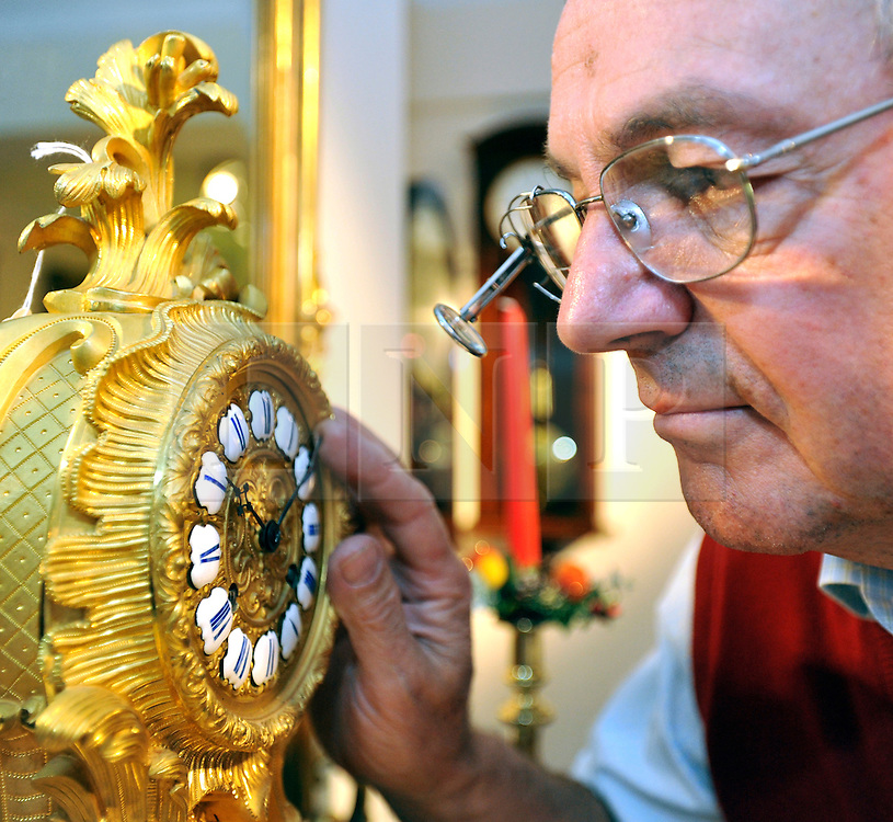 """©London News pictures...28/10/2010.  Michael Tooke changes the time on striking skeleton clock (circa 1850) designed to look like York Minster. Staff at Horological Workshops start the task of changing the 100's of clocks at their store in Guildford, Surrey, UK. Micahel Tooke who has owned the store for 43 years and worked in the clock business all his life said. """"at this time of year we get alot of people who bring clocks in for repair after they have changed the time incorreectly by winding back the hands manually"""""""