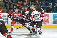 KELOWNA, CANADA, OCTOBER 26: Mackenzie Johnston #22 of the Kelowna Rockets checks Charles Inglis #15 of the Prince George Cougars with Taylor Thompson #25 as  Prince George Cougars visit the Kelowna Rockets  on October 26, 2011 at Prospera Place in Kelowna, British Columbia, Canada (Photo by Marissa Baecker/Shoot the Breeze) *** Local Caption *** Mackenzie Johnston; Charles Inglis; Taylor Thompson;