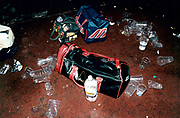 View of duffel bags and plastic cups on floor.