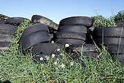 old tires stacked in grass field