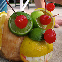 A cocktail served in a coconut decorated as a monkey head.