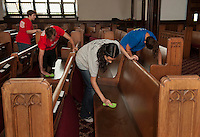 Up With People cast members Kelani Schumann, Jacob Dickson, Ana Ulibarri and Diane Goldsmith wash down pews in the Congregational Church Wednesday morning.  (Karen Bobotas/for the Laconia Daily Sun)
