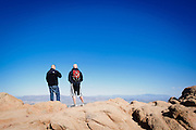 Two hikers look out on the Valley of the Sun from the top of Camelback Mountain.