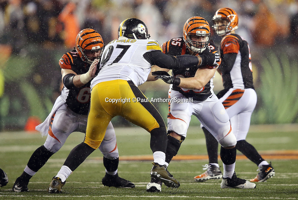 Cincinnati Bengals center Russell Bodine (61) and Cincinnati Bengals guard Clint Boling (65) double team pass block Pittsburgh Steelers defensive end Cameron Heyward (97) during the NFL AFC Wild Card playoff football game against the Pittsburgh Steelers on Saturday, Jan. 9, 2016 in Cincinnati. The Steelers won the game 18-16. (©Paul Anthony Spinelli)