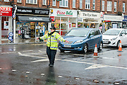 © Licensed to London News Pictures. 06/10/2014. Twickenham, UK. Police diverted traffic.  Firefighters help to contain a mains water pipe which has burst in King Street Twickenham today 6th October 2014. It appears that workmen working in the area have used a JCB digger to stem the flow. Many local shops and businesses have been flooded.   Photo credit : Stephen Simpson/LNP