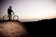 A mountain biker wearing a helmet standing on a hill above the ocean at dusk in Santa Barbara, California.(releasecode: jk_mr1026) (Model Released)