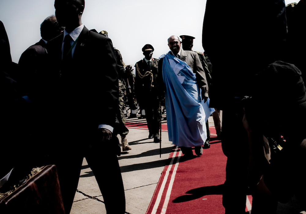 Sudanese President Omar Al-Bashir is flanked by security guards upon his arrival at Juba International Airport in Southern Sudan. Bashir is in town for a one day visit with Southern Sudanese politicians. Southern Sudan will vote on January 9 to decide whether or not to remain as part of Sudan or set off alone as the world's newest country. (© William B. Plowman)
