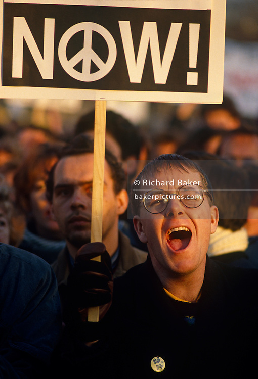 With mouth wide open in mid-shout, a young protester screams his anti-war message to the outside world during a large demonstration against the first Gulf War of 1991. He holds a placard with the now famous Peace Symbol, originally designed in 1958 for the British nuclear disarmament movement, designed by British artist Gerald Holtom for the march planned by the Direct Action Committee Against Nuclear War (DAC) from Trafalgar Square, London to the Atomic Weapons Research Establishment at Aldermaston. The symbol was later adopted by the Campaign for Nuclear Disarmament (CND), and subsequently became an international emblem for the 1960s anti-war movement and the counterculture of the time.
