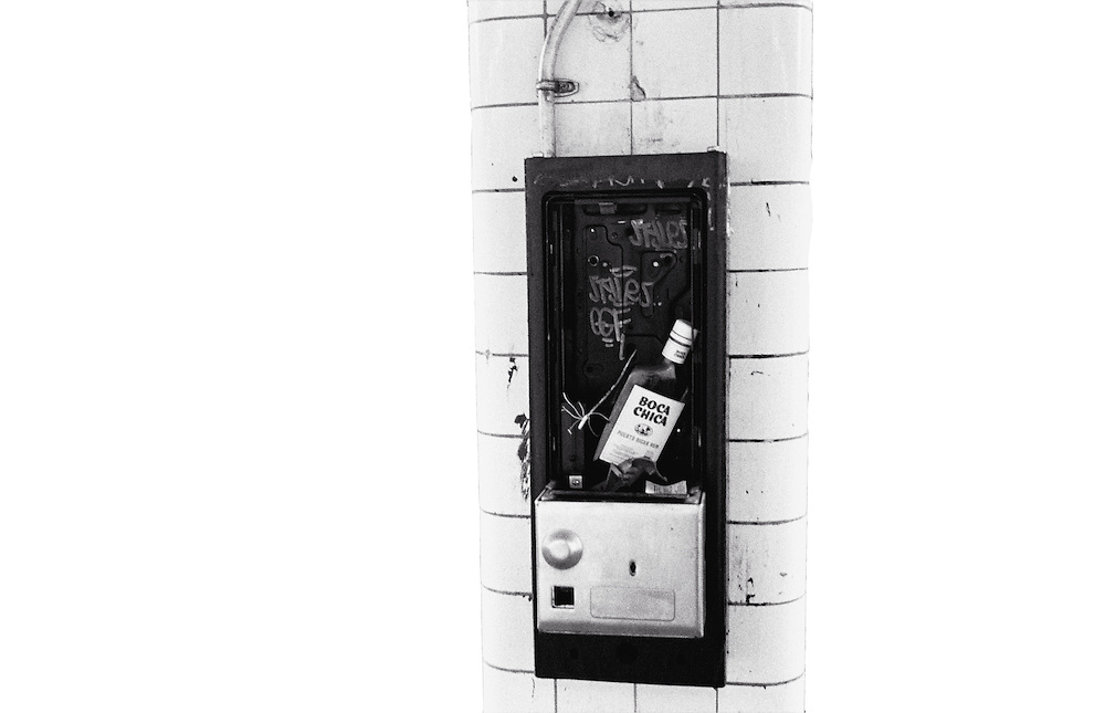 Rum bottle in place of pay telephone in Morgan Avenue subway station, Brooklyn, New York, 2005.