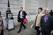 City workers walk past Evening Standards with Prime Minister Theresa May on the front page, asking the nation to trust her and yesterday's snap election announcement, outside the Bank of England in the heart of the capital's financial district, on 19th April, in the City of London, England.