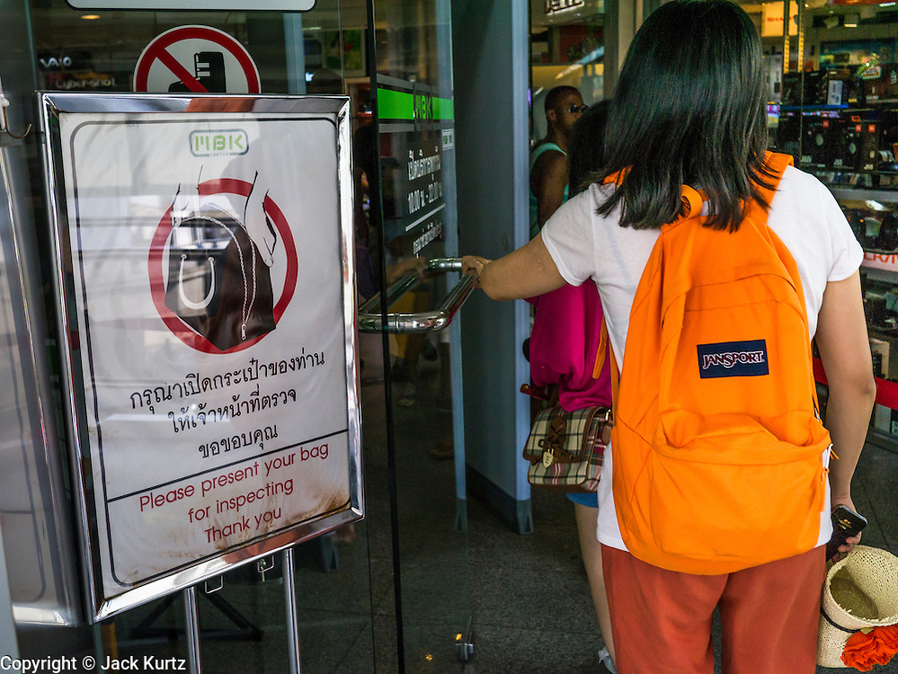 04 APRIL 2013 - BANGKOK, THAILAND:  Shoppers go past a sign announcing bag inspection in a Bangkok shopping mall. The United States' Federal Bureau of Investigation (FBI)  has warned the Thai government that Thailand has the greatest risk of a terror attack in Asia and the fifth greatest in the world. According to a statement from the Thai government the assessment is based on Thailand's relative freedoms and ease of movement in Thailand. In response to the report, Deputy Prime Minister Chalerm Yubamrung announced plans to set up an anti-terror center in Bangkok and work with Thai immigration to institute tougher screening on foreigners entering Thailand. In February 2012, terrorists thought to be connected with the Iranian government were arrested in Bangkok after the house they were living in blew up. At the time, Thai authorities said they suspected it was a bomb factory.     PHOTO BY JACK KURTZ