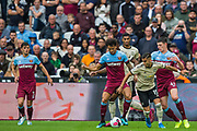 Andreas Pereira (Man United) in possession of the ball with Aaron Cresswell (West Ham) & Declan Rice (West Ham) either side during the Premier League match between West Ham United and Manchester United at the London Stadium, London, England on 22 September 2019.