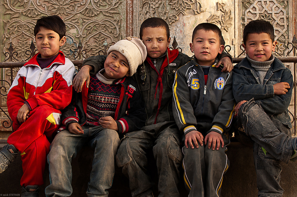— After being led through a labyrinth of back alleyways by a group of girls who wanted their picture taken, these Uyghur boys scrambled together into a moment for their own group portrait.