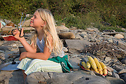 A girl at a picnic on the beach, looking through a pair of tongs.
