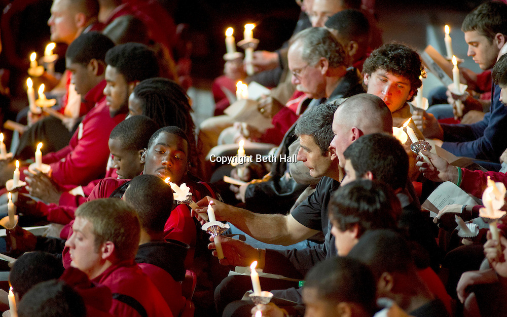 Nov 21, 2011; Fayetteville, AR, USA; Members of the Arkansas Razorback football team pass a flame during a memorial service for Arkansas Razorback tight end Garrett Uekman (88) at Bud Walton Arena. Mandatory Credit: Beth Hall-US PRESSWIRE