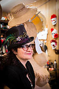 "Dina ""Cha Cha"" Pisani wearing a decorated straw top hat, and surrounded by her creations, in her shop."