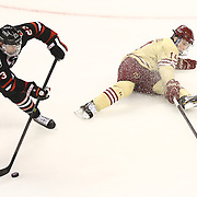 Colton Saucerman #23 of the Northeastern Huskies skates with the puck past Ryan Fitzgerald #19 of the Boston College Eagles during The Beanpot Championship Game at TD Garden on February 10, 2014 in Boston, Massachusetts. (Photo by Elan Kawesch)