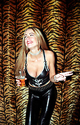 A female DJ wearing a tight PVC, rubber outfit holding a pint of beer, Roar, Evolution, Cardiff, Wales, 2001