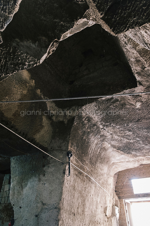 NAPLES, ITALY - 1 AUGUST 2018: A view of the ceiling in the garage of Cantina del Gallo, a family-owned restaurant in the Rione Sanità in Naples, Italy, on August 1st 2018. The garage is located inside a huge cave dug into the soft tufa stone. First excavated by the Romans, this now urban grotto was used in the Second World War as a shelter during aerial bombings.<br /> <br /> Cantina del Gallo, in the Rione Sanità, was established in 1898 and run by four generations of the Silvestri family. The cantina began as a store selling bulk wine and oil. It was only in the 1950s, when the legendary Aunt Cuncetta began cooking, that it became the simple and genuine tavern it is today.<br /> There are three dishes that are the restaurant's workhorses, and the ones we always seem to rotate between: the pennette alla sorrentina (a variation of the classic gnocchi alla sorrentina, seasoned with tomato, basil and stringy mozzarella), the baked cod (although the fried cod is just as mouth-watering) and the pizza cafona (peasant pizza), topped with oregano, cheese, chile and with double the tomatoes (tomato juice and chopped tomatoes).