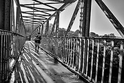 """A woman makes her way across the Malancthon pedestrian bridge that connects the """"Below-the-Tracks"""" neighborhood of Riverside in Hazelwood, Pa.<br /> <br /> Hazelwood reached a peak population of 13,000 residents in 1960, its main street lined with grocery stores, butcher shops, bakeries, banks and some 41 bars along a 3.5 mile stretch down the main business district of the city. It has been home to a variety of ethnicities including people of Hungarian, Italian, Slovak, Polish, Irish and African-American descent. The neighborhood had a population of 4,317 in 2010, according to the U.S. Census.<br /> <br /> <br /> Spurred on by the Pittsburgh-based riverfront investment organization ALMONO's new development on its northside, many residents in Riverside, in particular have created interest in building their community back up. While there is no fully restoring their town to its glory days during the steel age, residents are interested in bettering their neighborhood for a new and more innovative age."""