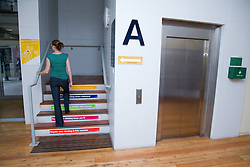 "Officer worker climbing the stairs instead of using the lift to emphasise the ""Keep fit use the stairs campaign"","