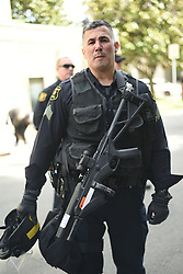 April 27, 2017 - Berkeley, California, U.S - A Berkeley police officer looks on as alt-right activists and Trump supporters equipped in helmets, football pads and other gear rally in the Berkeley's Civic Center Park). Violence has broken out between Trump supporters and black bloc antifascists at several events in the city this year. Coulter cancelled her visit when she and the University of California-Berkeley, where she was scheduled to speak, could not agree on an appropriate date. (Credit Image: © Jeremy Breningstall via ZUMA Wire)