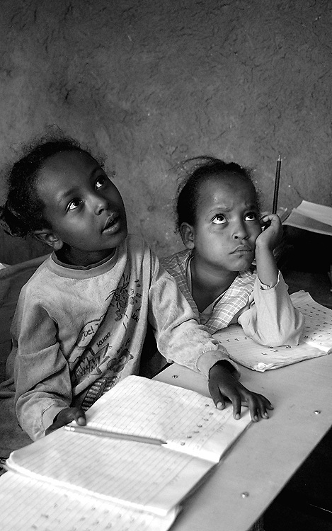 Two young Ethiopian girls pay close attention to their teacher at their elementary school in Nazret, Ethiopia.