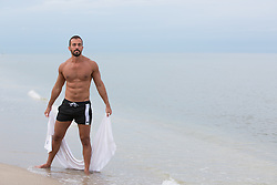 man at the beach holding a towel