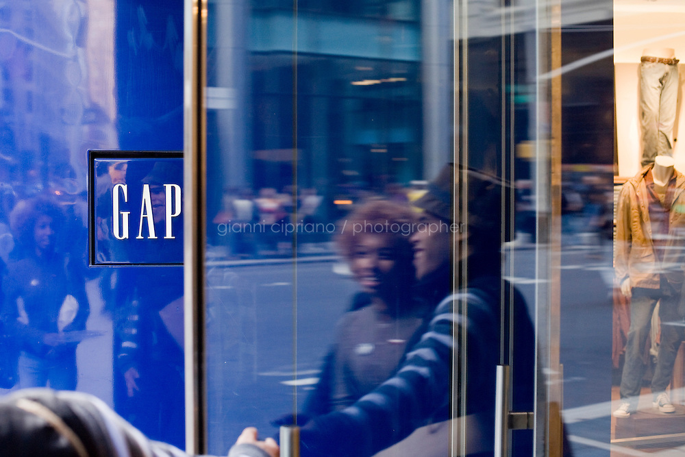 4 October, 2008. Customers enter the gap store of 59th street and Lexington ave. As the financial crisis spread last month, many retailers hit the panic button, offering more generous discounts than they did at the same time last year. But the promotions did little to convince cautious shoppers to open their wallets.<br /> <br /> ©2008 Gianni Cipriano for The Wall Street Journal<br /> cell. +1 646 465 2168 (USA)<br /> cell. +1 328 567 7923 (Italy)<br /> gianni@giannicipriano.com<br /> www.giannicipriano.com