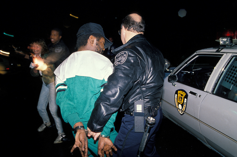 USA, Alaska, Anchorage, Police officer arrests African-American man on drug charges in downtown at night