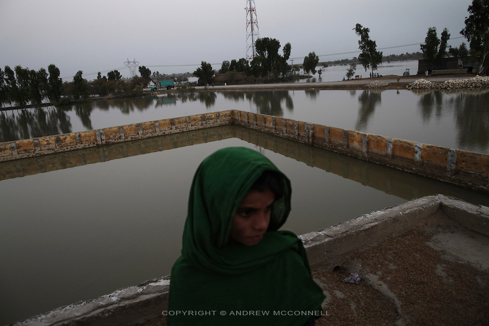 A girl seeks refuge on the roof of a school near Karampur, Sindh province, Pakistan.