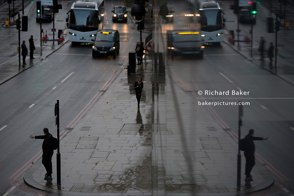 A pedestrian hails a taxi on Upper Thames Street in the City of London, the capital's financial district - aka the Square Mile, on 7th November 2018, in London, England.