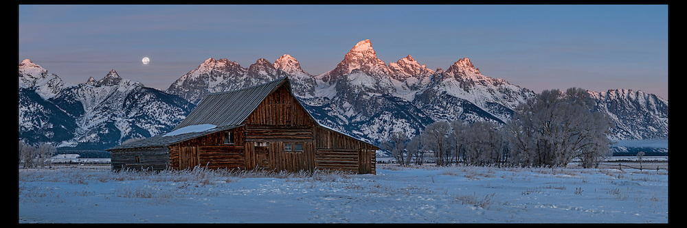 First light on the Grand Teton mountain range as the Winter moon sets. Historic Moulton barn awaits the morning light.