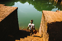 A man fetches water from a large pool outside of  a mosque in Goa, India.
