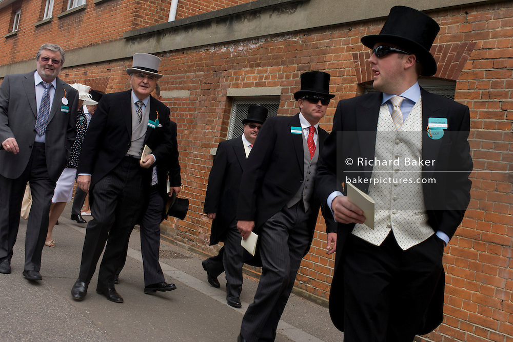 Formally-dressed gentlemen arrive at the racecourse during the annual Royal Ascot horseracing festival in Berkshire, England. Royal Ascot is one of Europe's most famous race meetings, and dates back to 1711. Queen Elizabeth and various members of the British Royal Family attend. Held every June, it's one of the main dates on the English sporting calendar and summer social season. Over 300,000 people make the annual visit to Berkshire during Royal Ascot week, making this Europe's best-attended race meeting with over £3m prize money to be won.