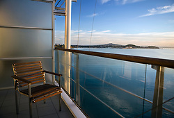 A lone deck chair sits on a balcony overlooking Waitemata Harbour with Mount Victoria and North Head in the background, Auckland, New Zealand