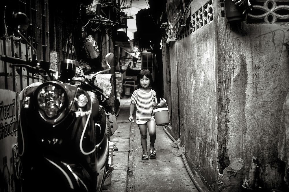 A child is carrying a bucket of ice for soft drinks in the sweltering heat of the Khlong Toei district of Bangkok, Thailand.