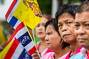 "05 MAY 2013 - BANGKOK, THAILAND:   Thais hold the Thai flag and King's flag while they wait to see Bhumibol Adulyadej, the King of Thailand, Sunday. The King and Queen, who are both hospitalized and in poor health, did not attend Sunday's event. May 5 marks the 63rd anniversary of the Coronation of His Majesty King Bhumibol Adulyadej. The day is celebrated as a national holiday; since this year it falls on a Sunday, it will be observed on Monday May 6, and as such all government offices and commercial banks will close for the day. HM King Bhumibol Adulyadej is the longest reigning monarch in the world. Each year on the 5th of May, the Kingdom of Thailand commemorates the day when, in 1950, the Coronation Ceremony was held for His Majesty King Bhumibol Adulyadej, the 9th in the Chakri Dynasty (Rama IX). On the 5th of May, His Majesty conducts a merit making ceremony, presenting offerings to Buddhist monks, and leads a ""Wien Thien"" ceremony, walking three times around sacred grounds at the Temple of the Emerald Buddha.    PHOTO BY JACK KURTZ"
