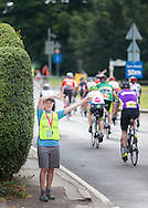 A volunteer signals a right turn ahead for cyclists as they ride through the Surrey countryside at Abinger Hammer during the Prudential RideLondon-Surrey 100, Sunday 2nd August 2015. <br /> <br /> Prudential RideLondon is the world&rsquo;s greatest festival of cycling, involving 95,000+ cyclists &ndash; from Olympic champions to a free family fun ride - riding in five events over closed roads in London and Surrey over the weekend of 1st and 2nd August 2015. <br /> <br /> Photo: Christopher Ison for Prudential RideLondon<br /> <br /> See www.PrudentialRideLondon.co.uk for more.<br /> <br /> For further information: Penny Dain 07799 170433<br /> pennyd@ridelondon.co.uk